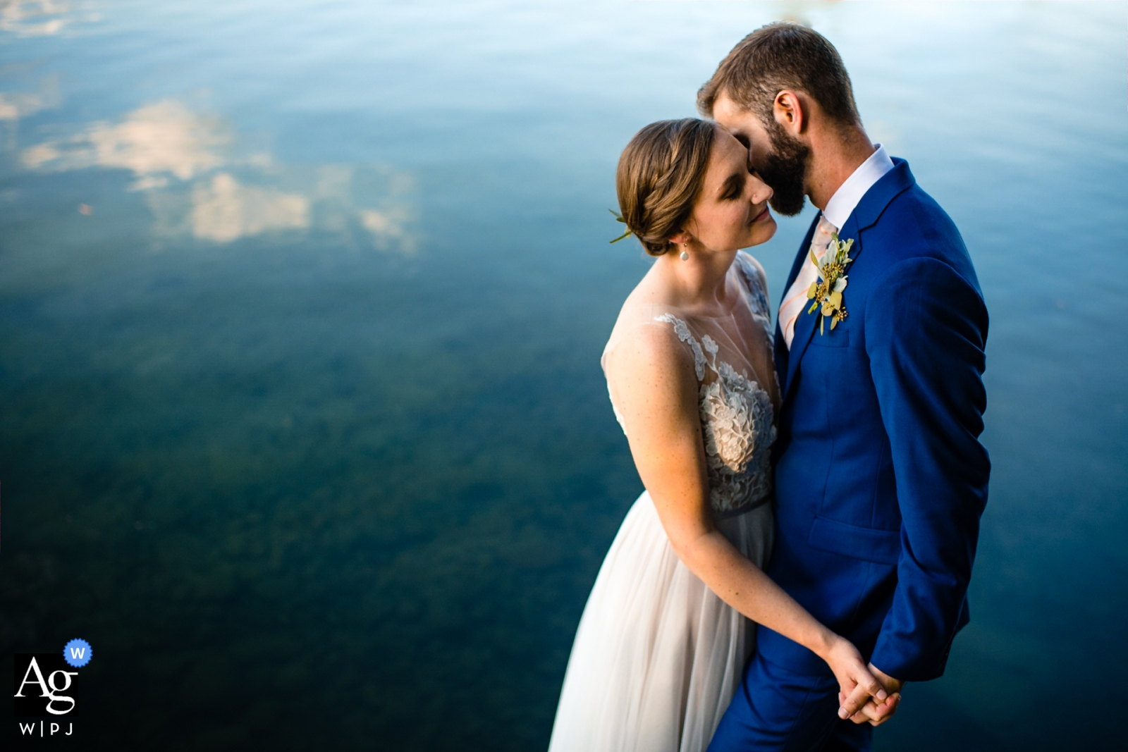 Oakland Maine camp manitou | Bride and groom pose at lake for wedding portraits