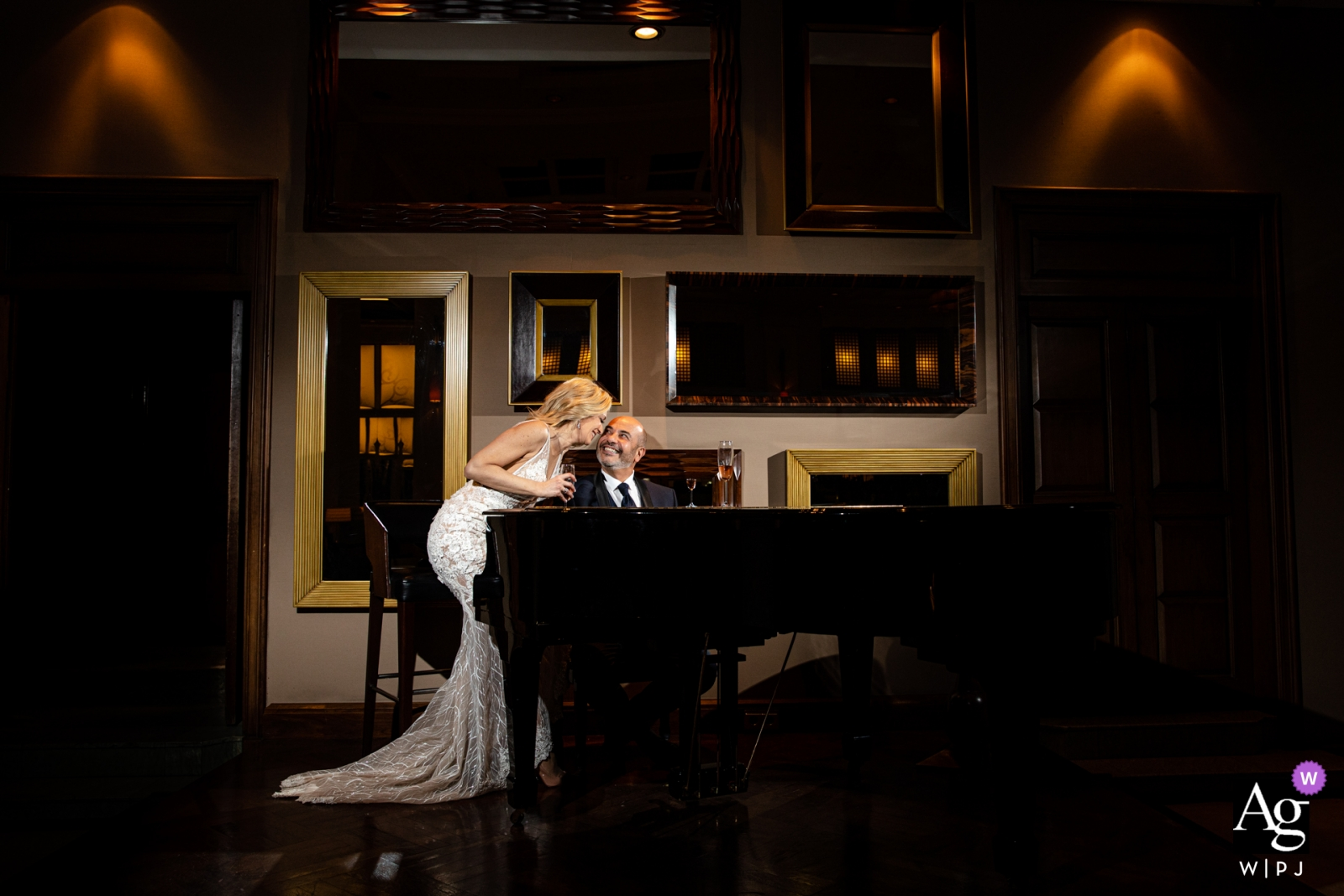 Swiss Hotel Bosphorus wedding photo | Groom is playing piano and the bride is sitting next to him and they are slaughtering and drinking champagne