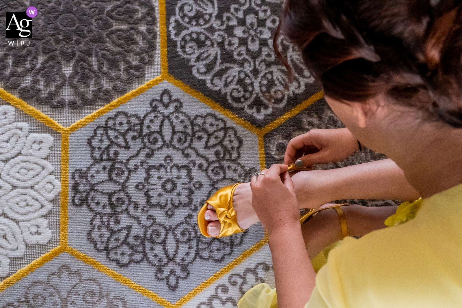Gouda, The Netherlands wedding photography | The sister of the bride is tying her yellow shoestraps on an yellow bordered honeycomb carpet