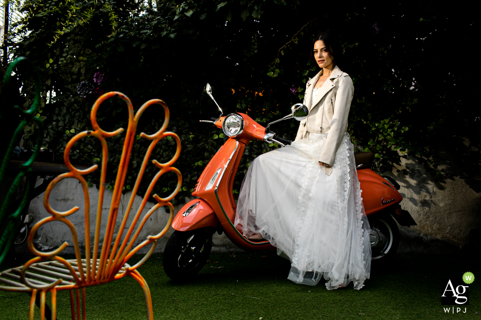 Grand Ankara Hotel wedding venue photography | Bride is sitting on a Vespa which is next to wall and looking at the camera