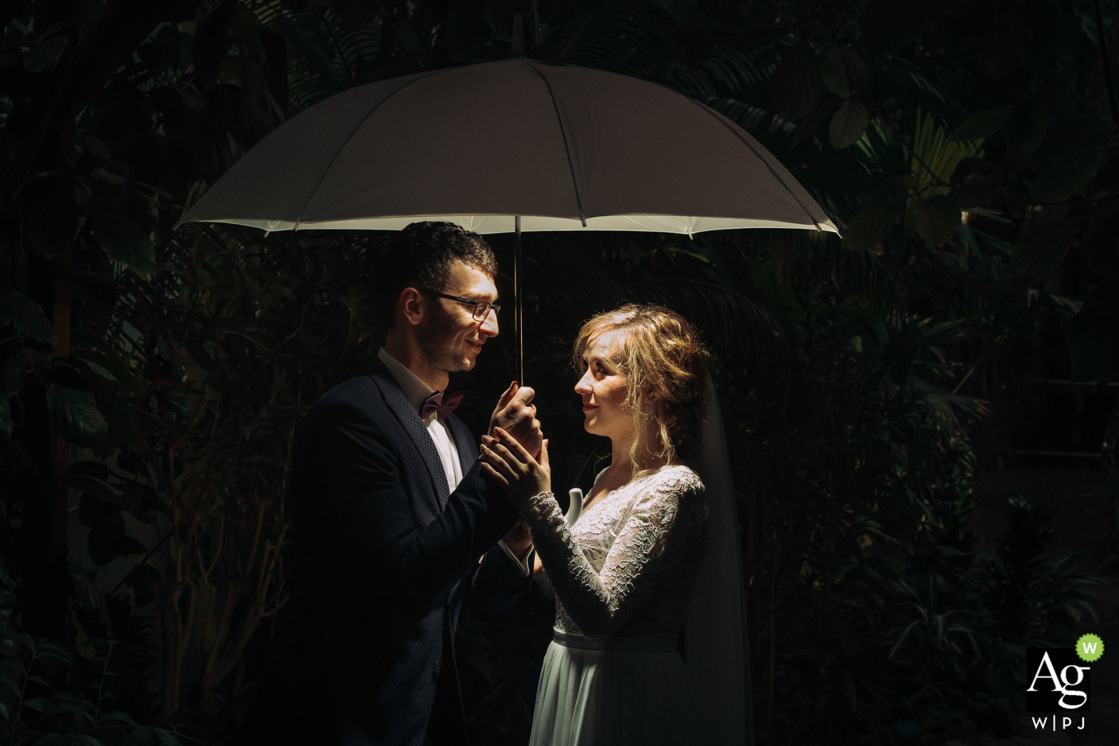 Church of Saint Albert Chmielowski in Lodz, Poland artistic wedding couple portrait of The bride and groom standing under an umbrella during a quick session after leaving the church