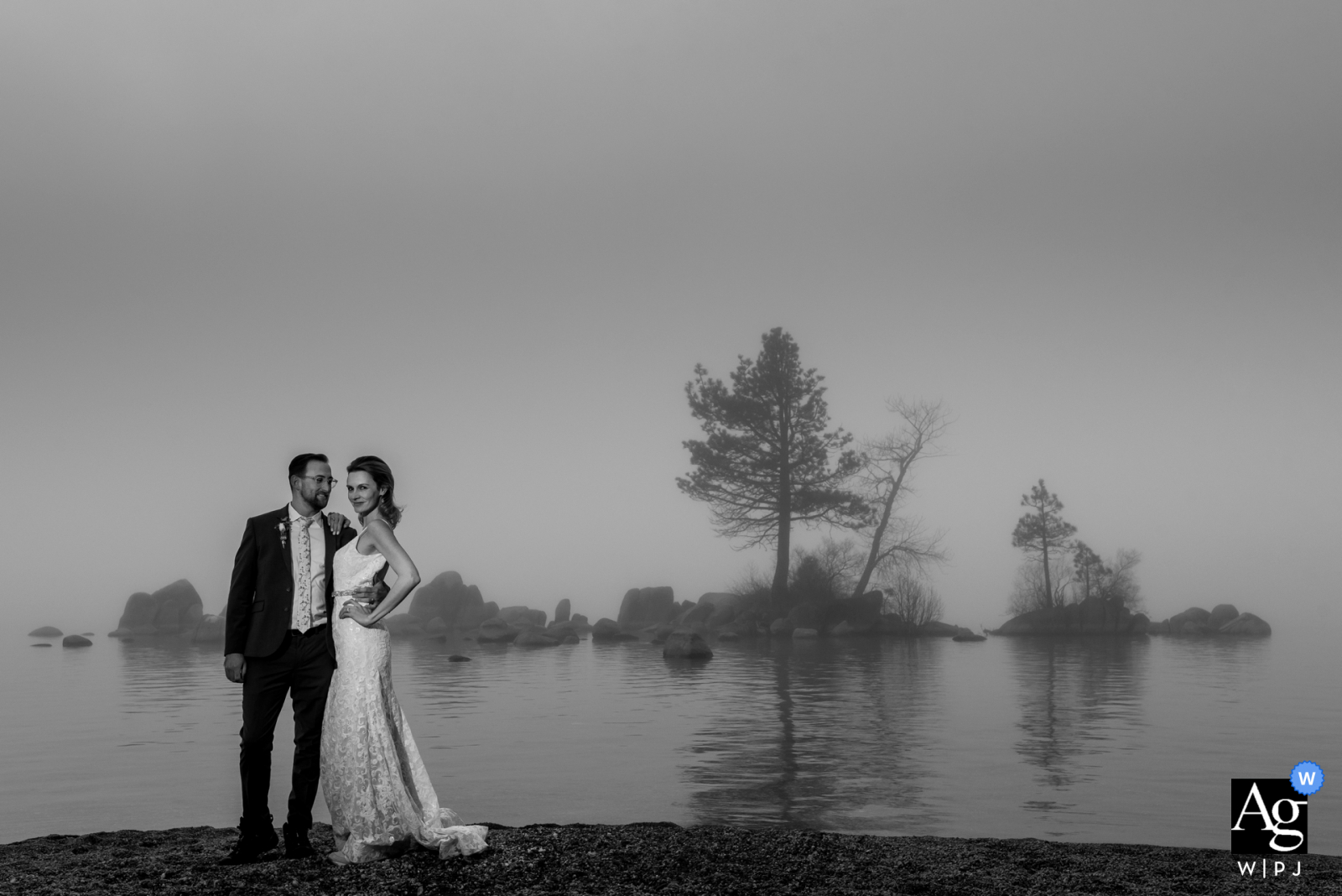 A bride and groom pose on the shores of Lake Tahoe, Zephyr Cove, surrounded by thick fog.