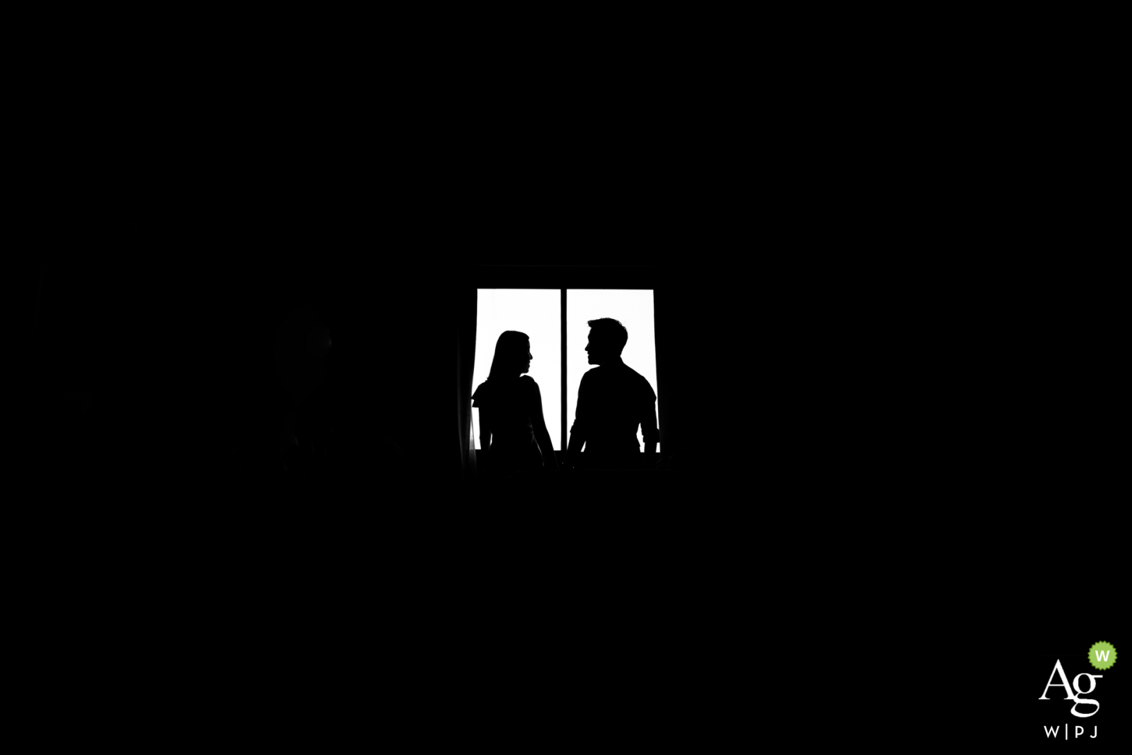 Samutprakarn black and white wedding portrait in a dark room against a window with a strong silhouette
