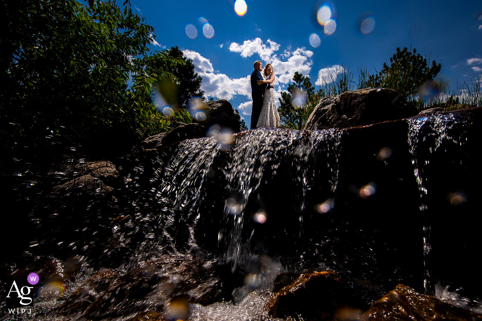 Bride and groom standing on top of waterfall at Spruce Mountain Ranch in Larkspur, CO
