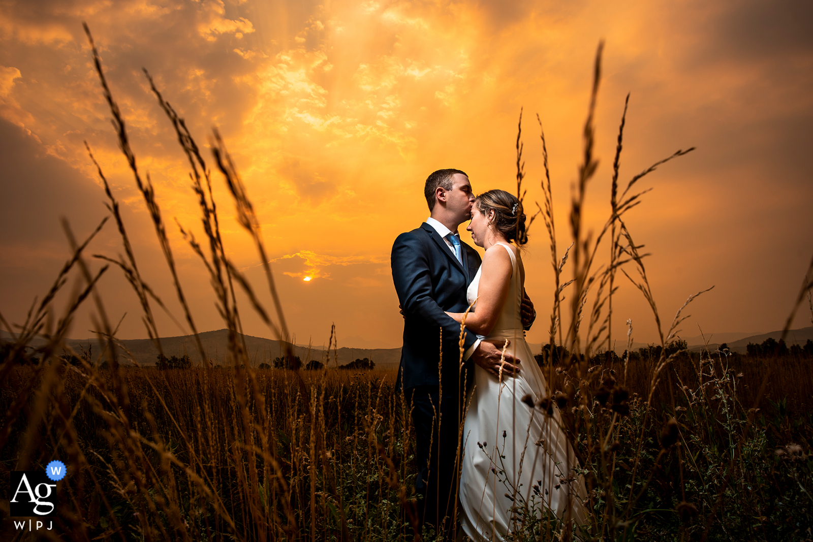 Bride and groom portrait against orange sky at the Shupe Homestead in Hygiene, CO