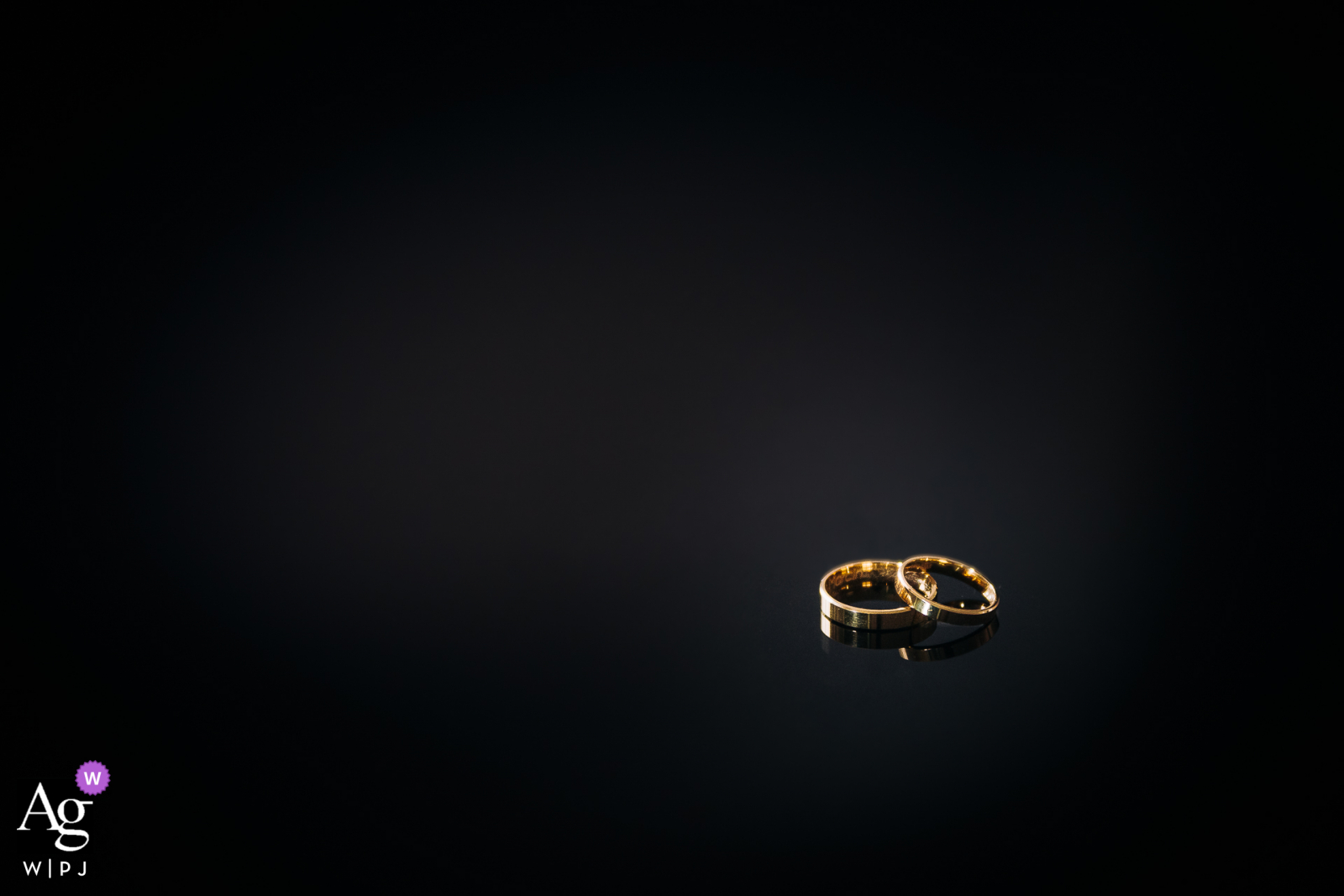 """A close-up of the wedding rings of the bride and groom lying on a dark table at the """"On the hill"""" Mansion in Lodz, Poland"""