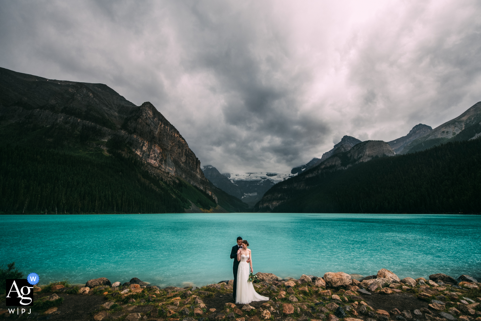 Lake Louise, Banff National Park, AB, Canada wedding couple posing for portraits while Standing in the rain