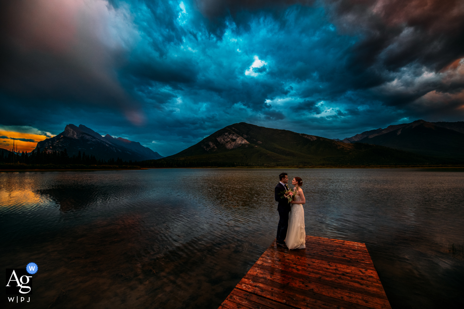 Vermilion Lakes, AB, Canadawedding day Sunset portrait of the bride and groom on a wooden dock