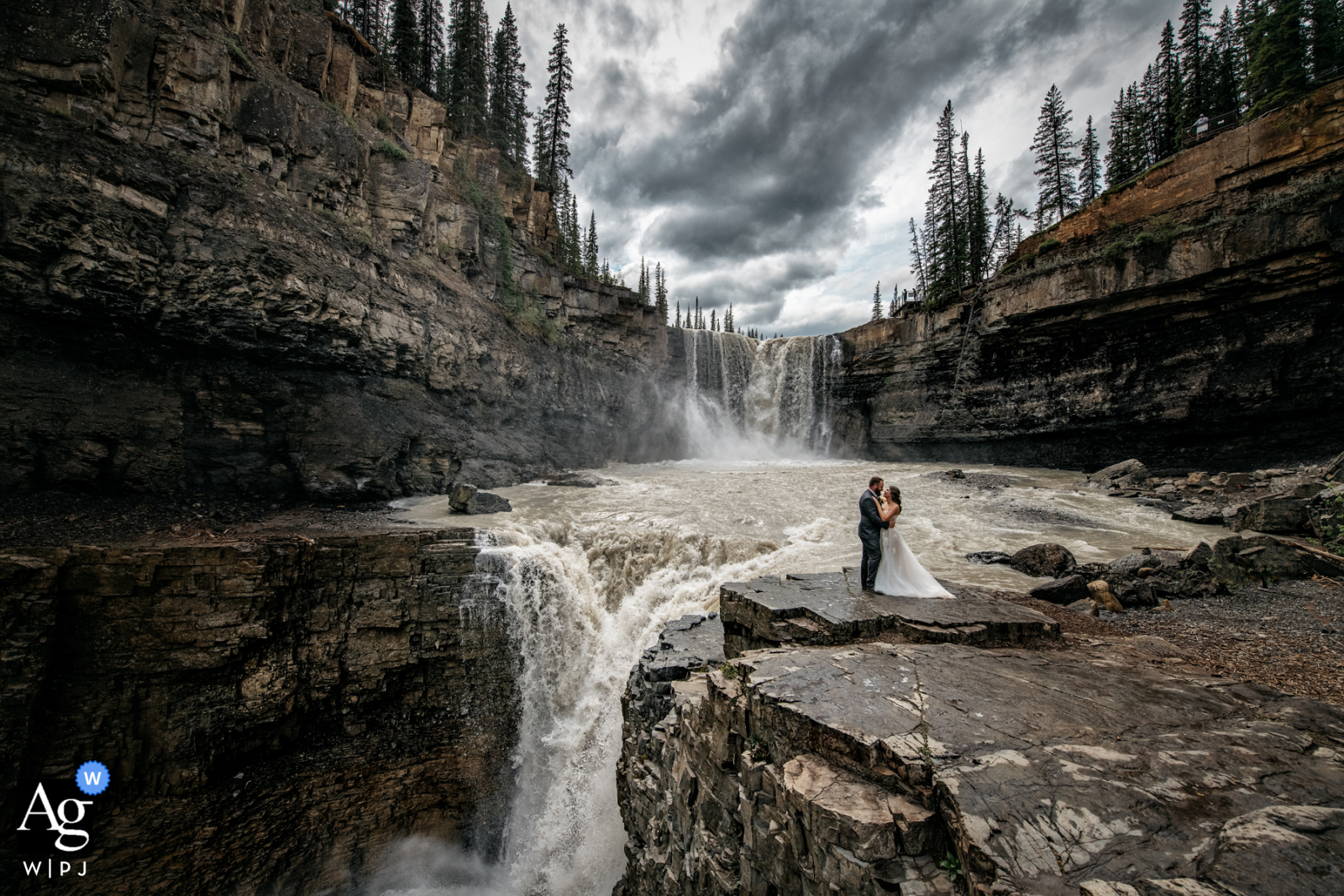 Artistic wedding photography at Crescent Falls, AB, Canada with a Hug at the waterfalls