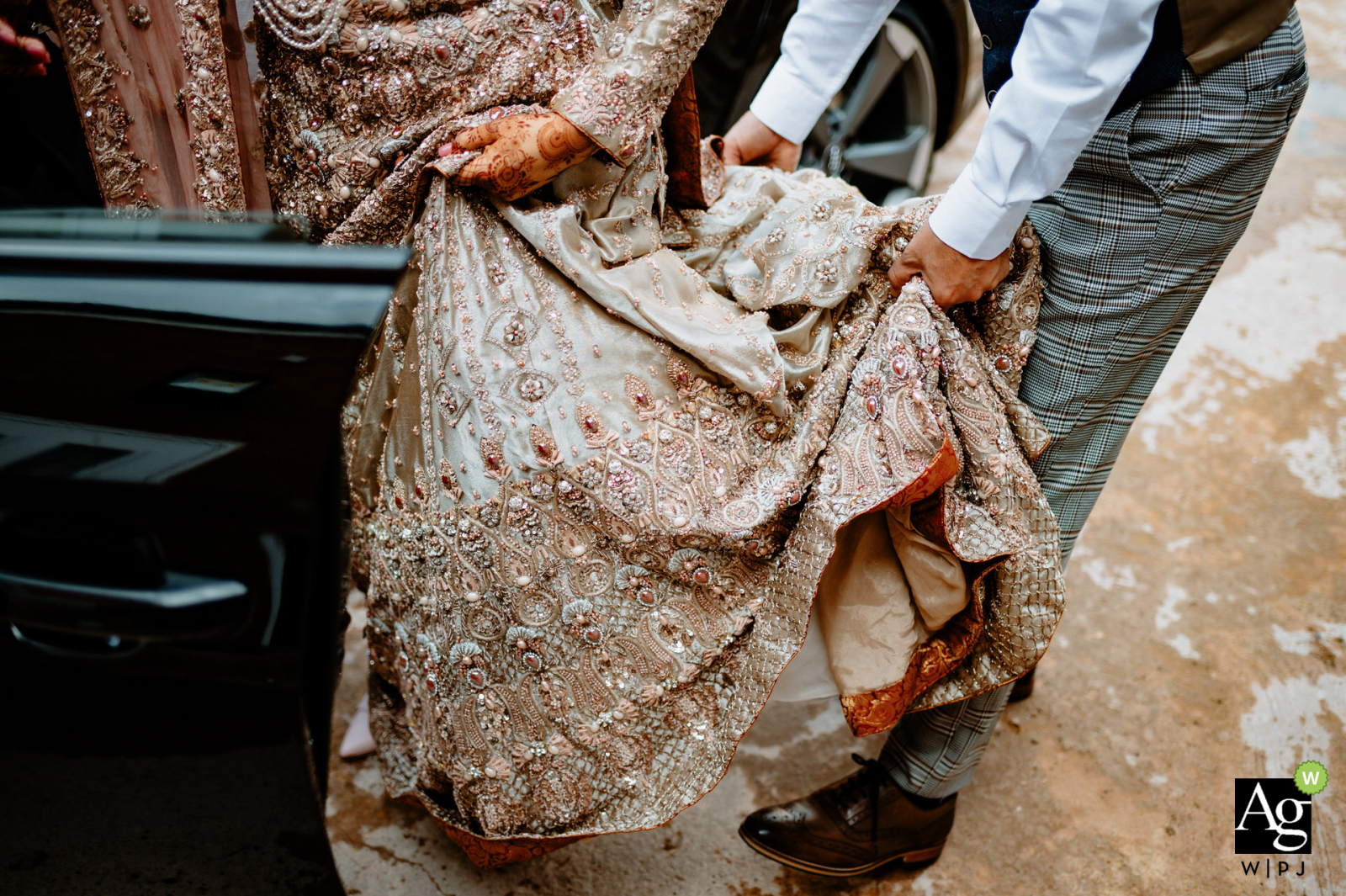 Birmingham, UK wedding reportage detail picture showing some Helping hands as the bride gets into an auto