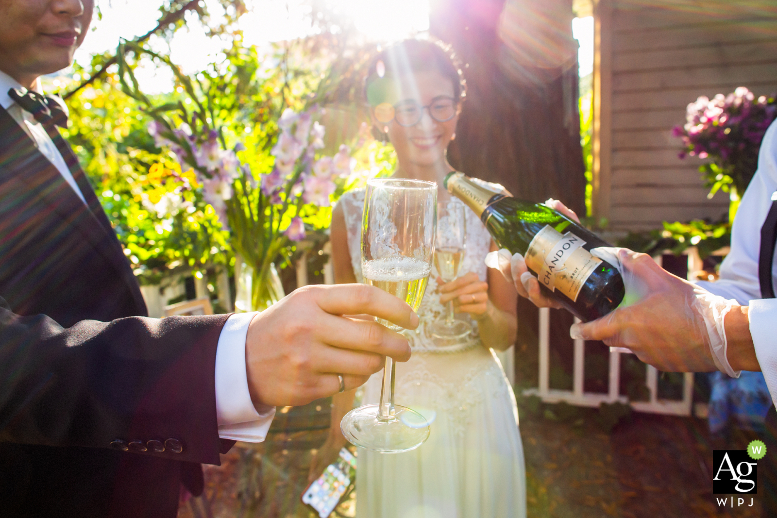 Oakland fine art wedding detail photography picture of some bottle pouring outside in the sunshine before a toast of Cheers
