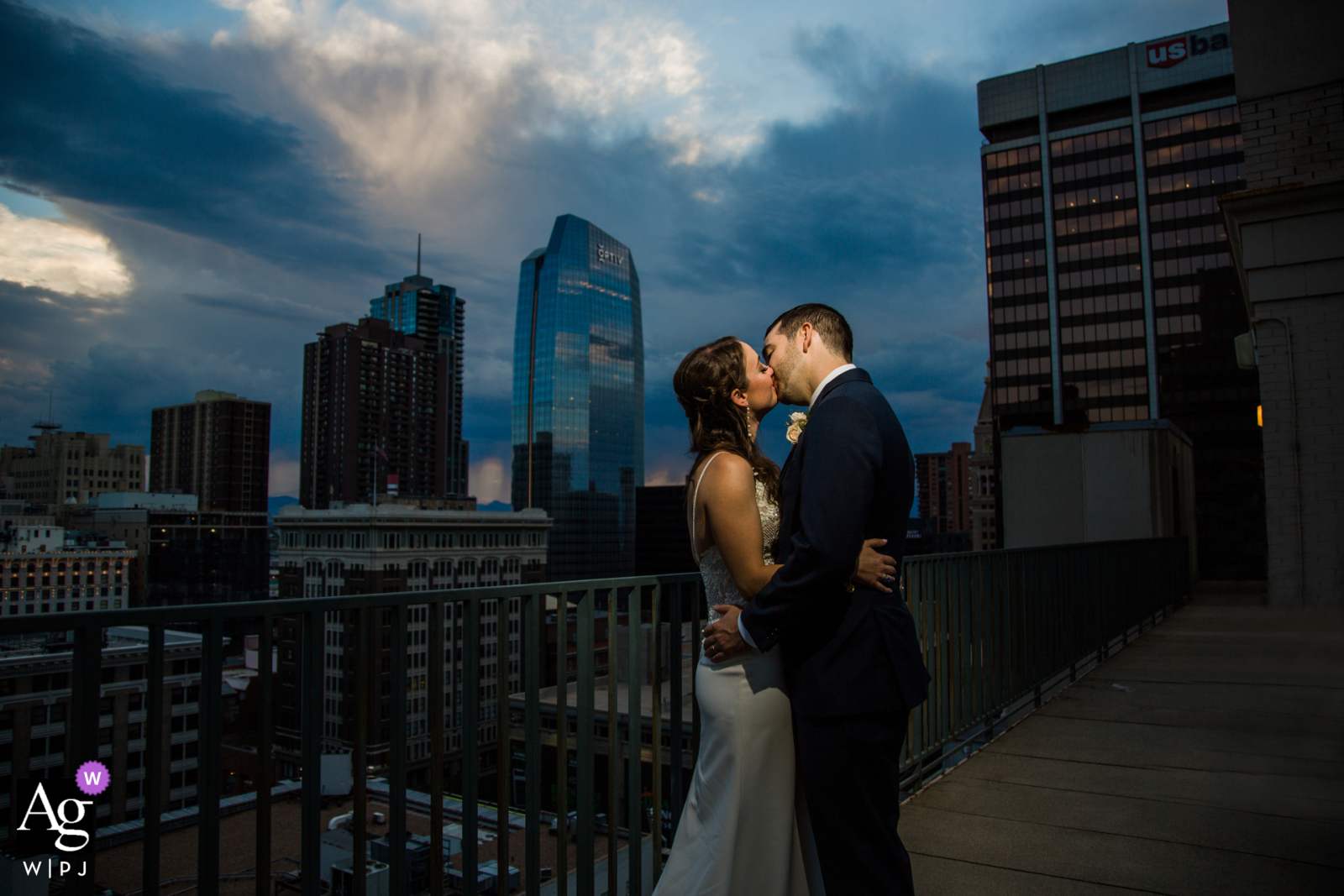Colorado couple kissing at sunset at top of the Magnolia Hotel in Denver