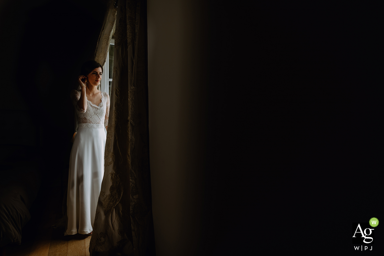 Auvergne-Rhône-Alpes wedding bride posing for a portrait next to a window opening with natural lighting