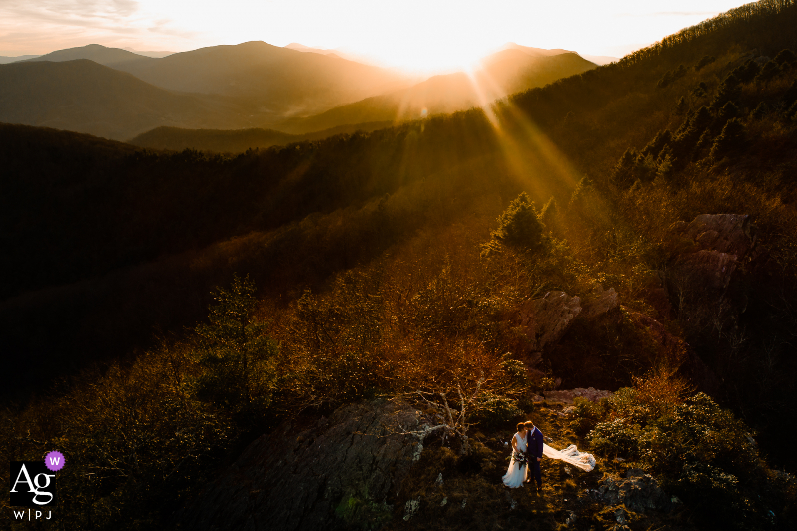"""Jefferson, North Carolina artistic wedding portrait at sunset. """"We were able to hike to the top of a Ridgeline, put the drone up in the air, and then position it perfectly where the sun was lighting them"""