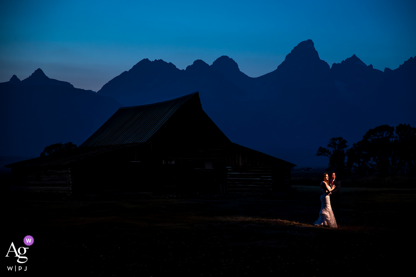Grand Teton National Park, Jackson, WY blue hour portrait of bride and groom by a barn