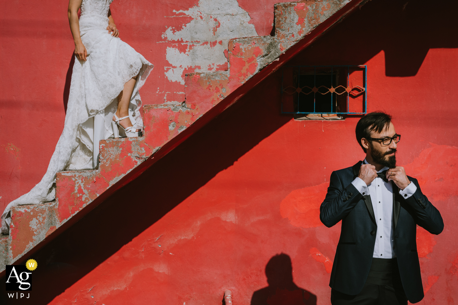 Istanbul wedding photographer captured a bride on the stairs and the groom down the stairs on a red background in Kadıköy