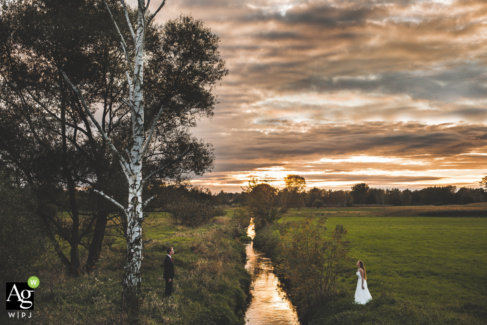 Grotniki, Lodzkie, Poland couple posing for a wedding picture over a small river with big trees and clouds