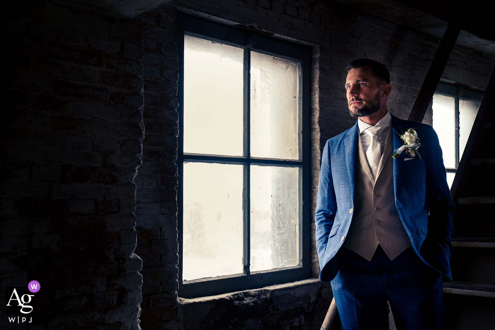 At the Sodafabriek old factory in Schiedam The Netherlands, The groom is standing in a cool pose on the stairs for an artistic wedding photo