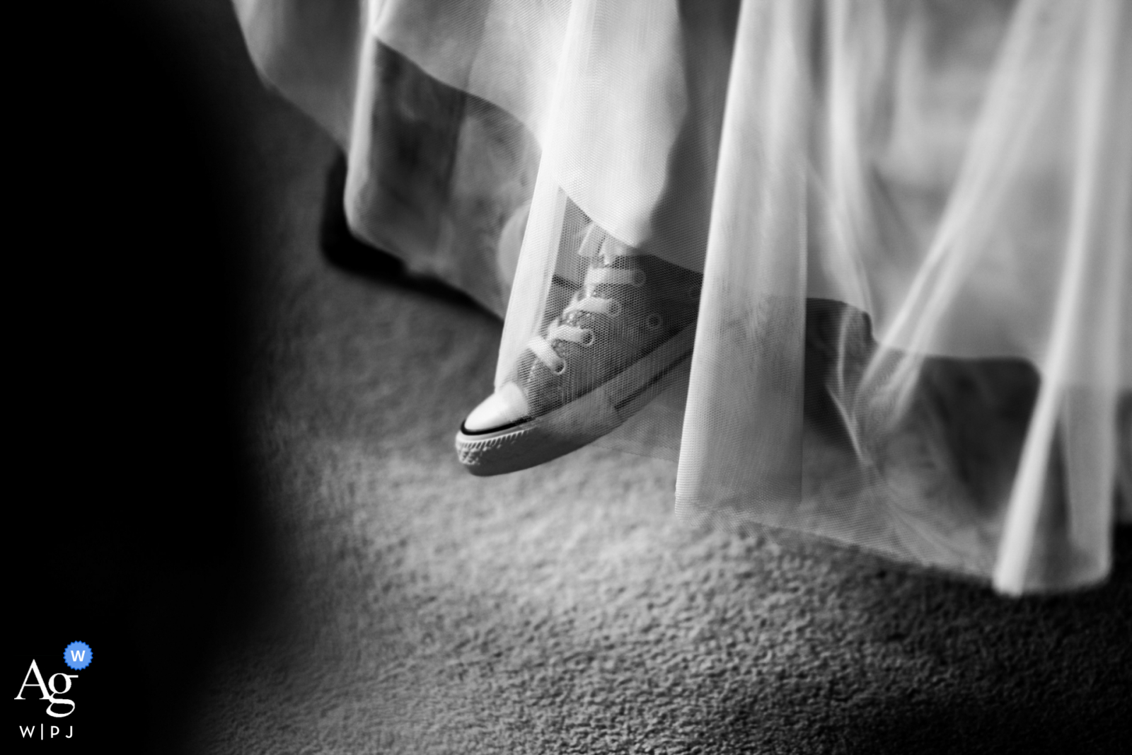 United Kingdom wedding photographer captures the feet of a flowergirl as she dangles her Converse off the bed