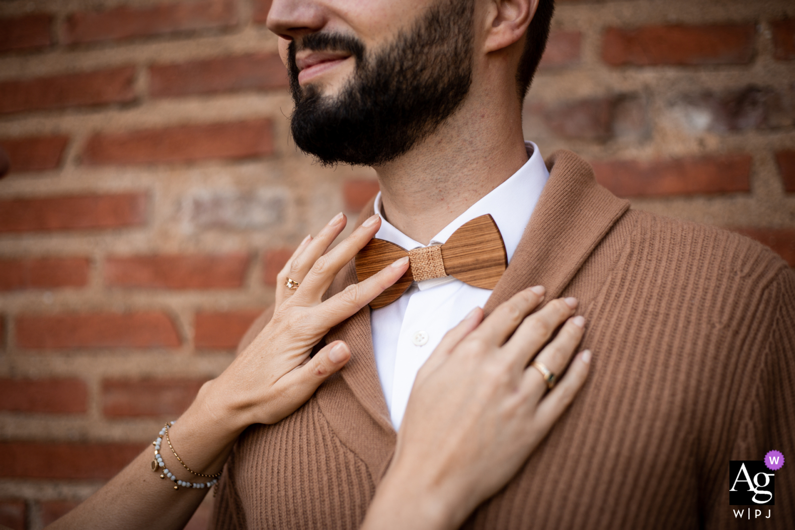 Albi street south of France creative wedding detail image of the grooms Wood bow tie against a warm brick wall and sweater