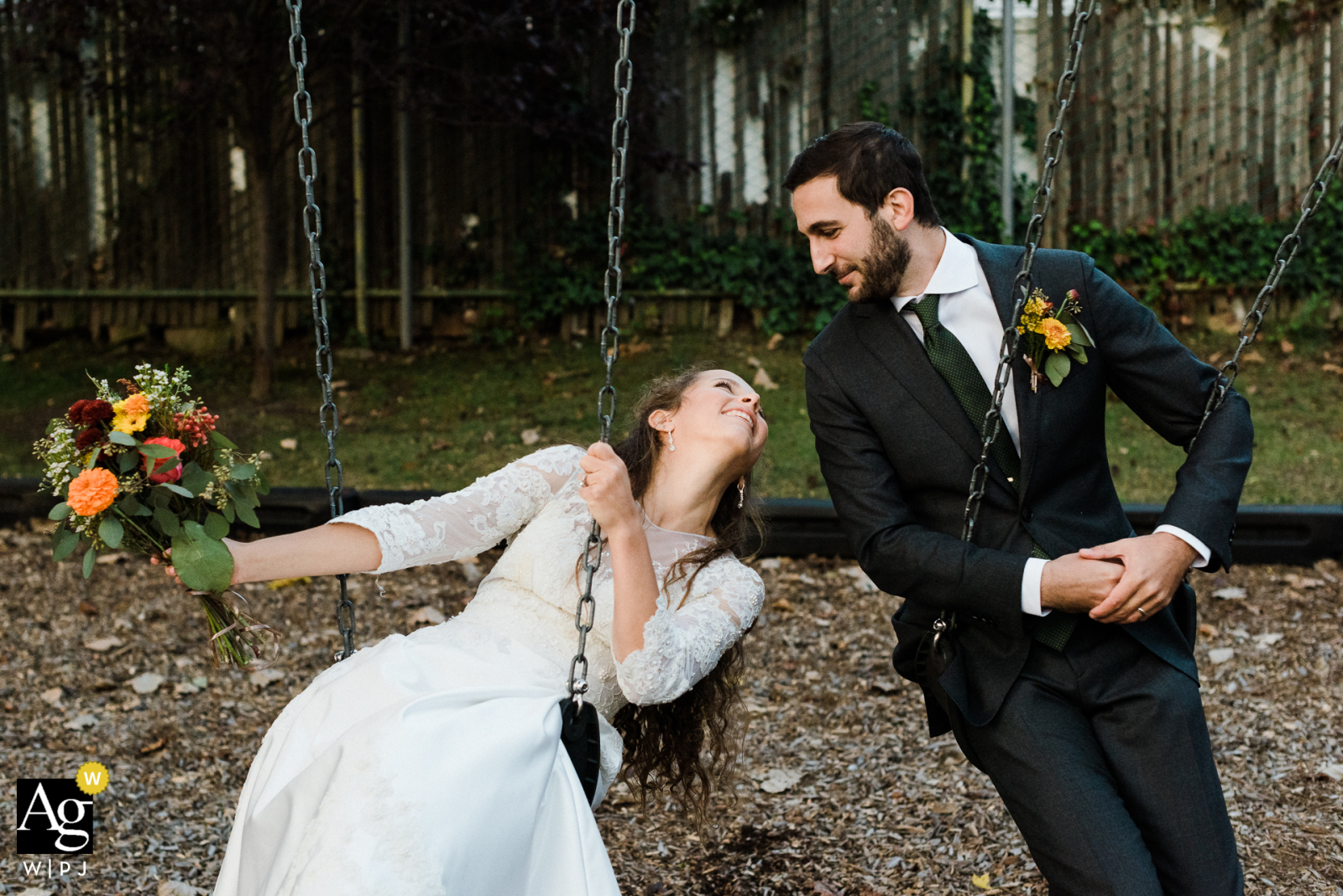 Long Island, New York, city park fine art wedding couple portrait of Two newlyweds playfully looking at each other as they swing on playground park swings
