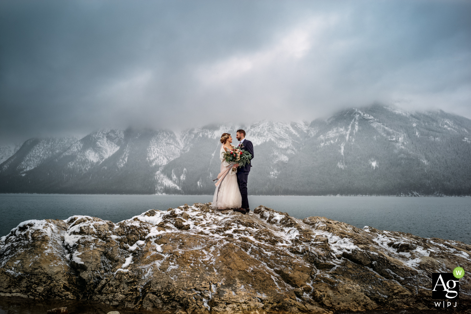 Lake Minnewanka, Banff National Park, AB, Canada wedding couple posed portrait session of the bride and groom holding each other amongst the snow-capped mountains