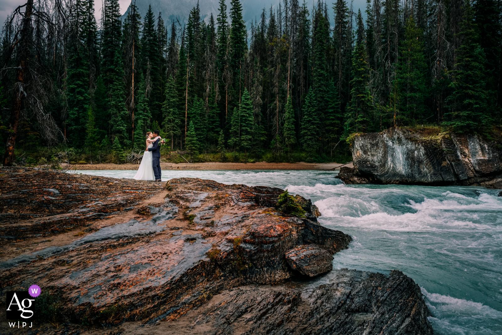 Natural Bridge, Field, BC, Canada fine art wedding couple portrait with a sweet Romantic kiss