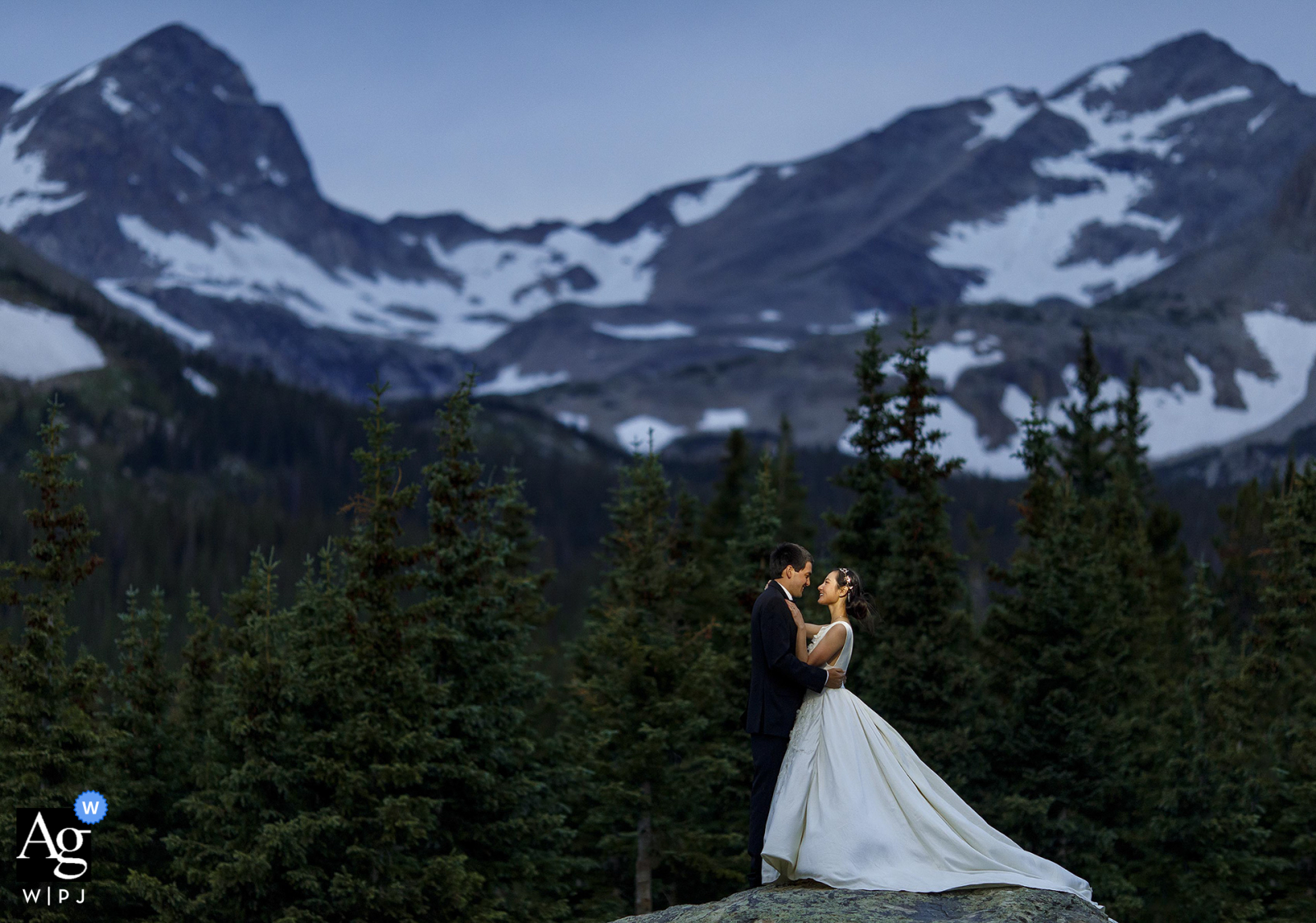 Brainard Lake, Ward, CO creative couple wedding portrait of the bride and groom posing together on a rock at twilight following their elopement