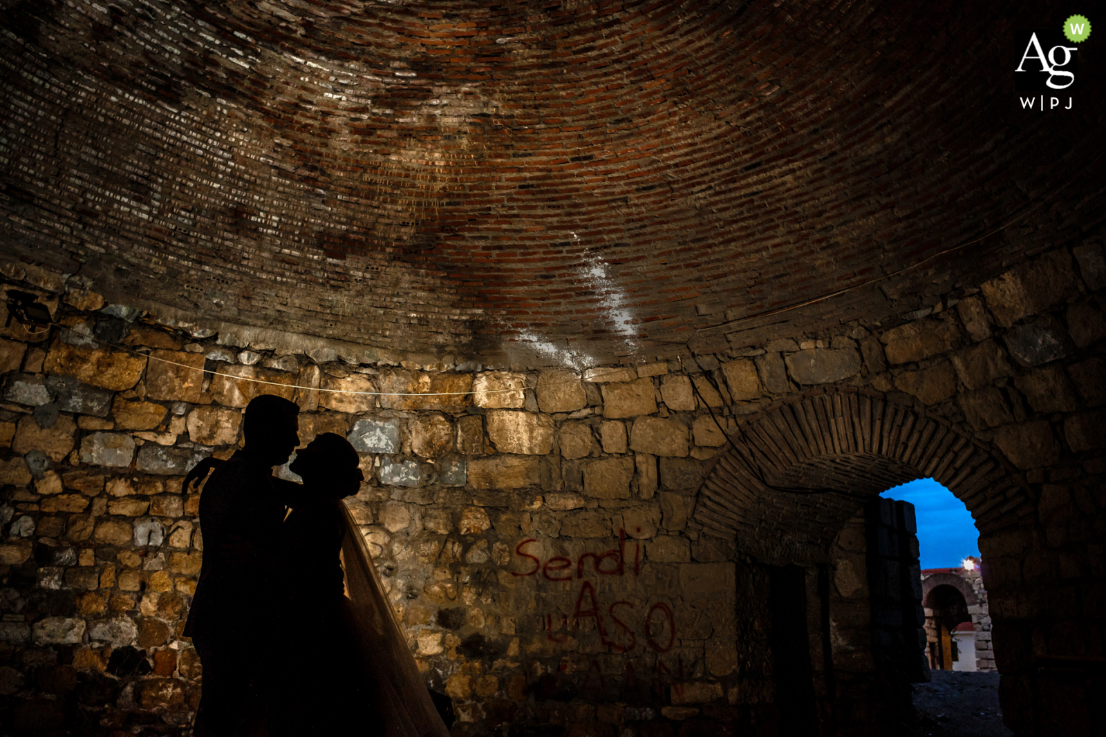 Seferihisar wedding couple portrait shoot of them silhouetted against a stone wall in Izmir