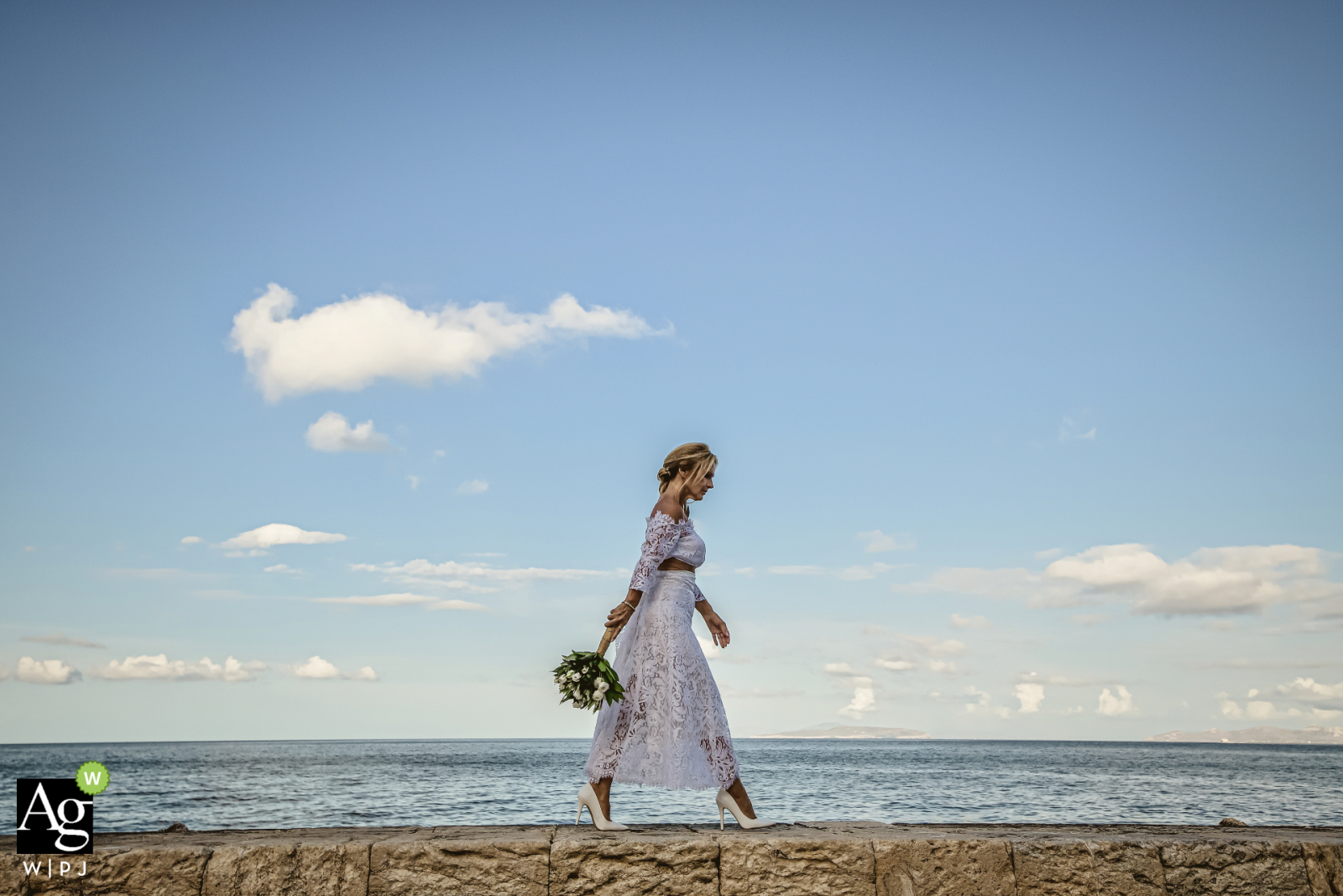 Tuscany bride walking for wedding portrait session on a wall at the beach