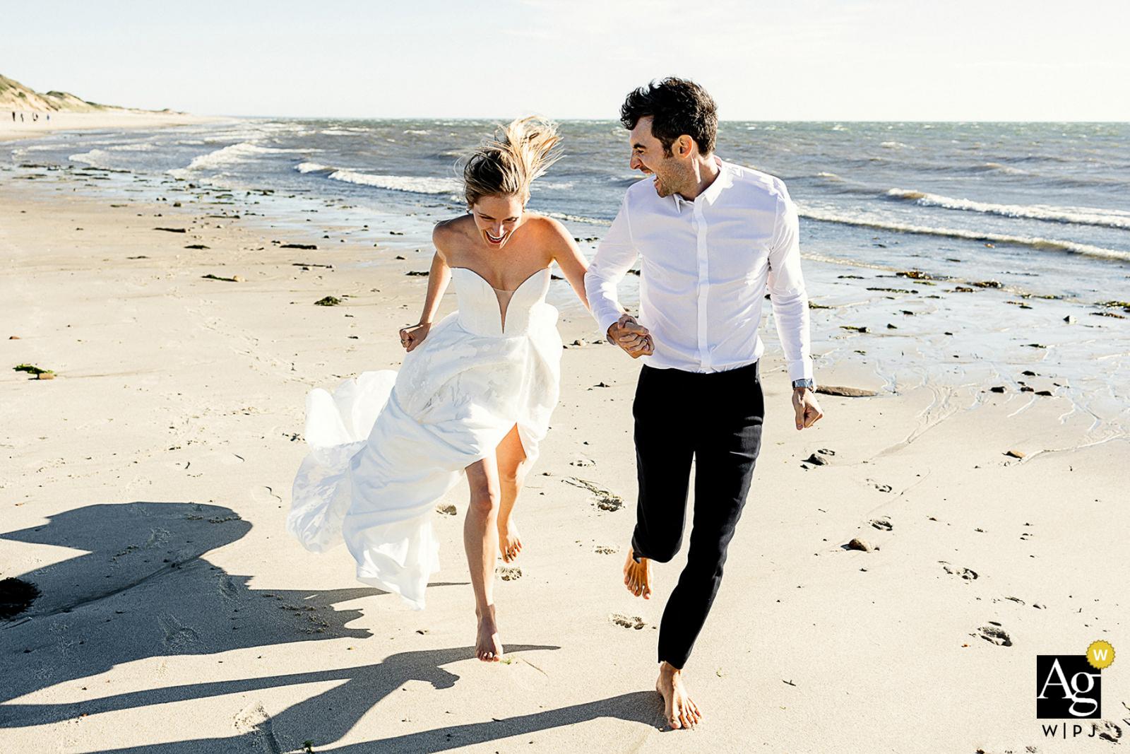 Wellfleet, MA creative beach sand running wedding image of the Bride and groom in the sunshine