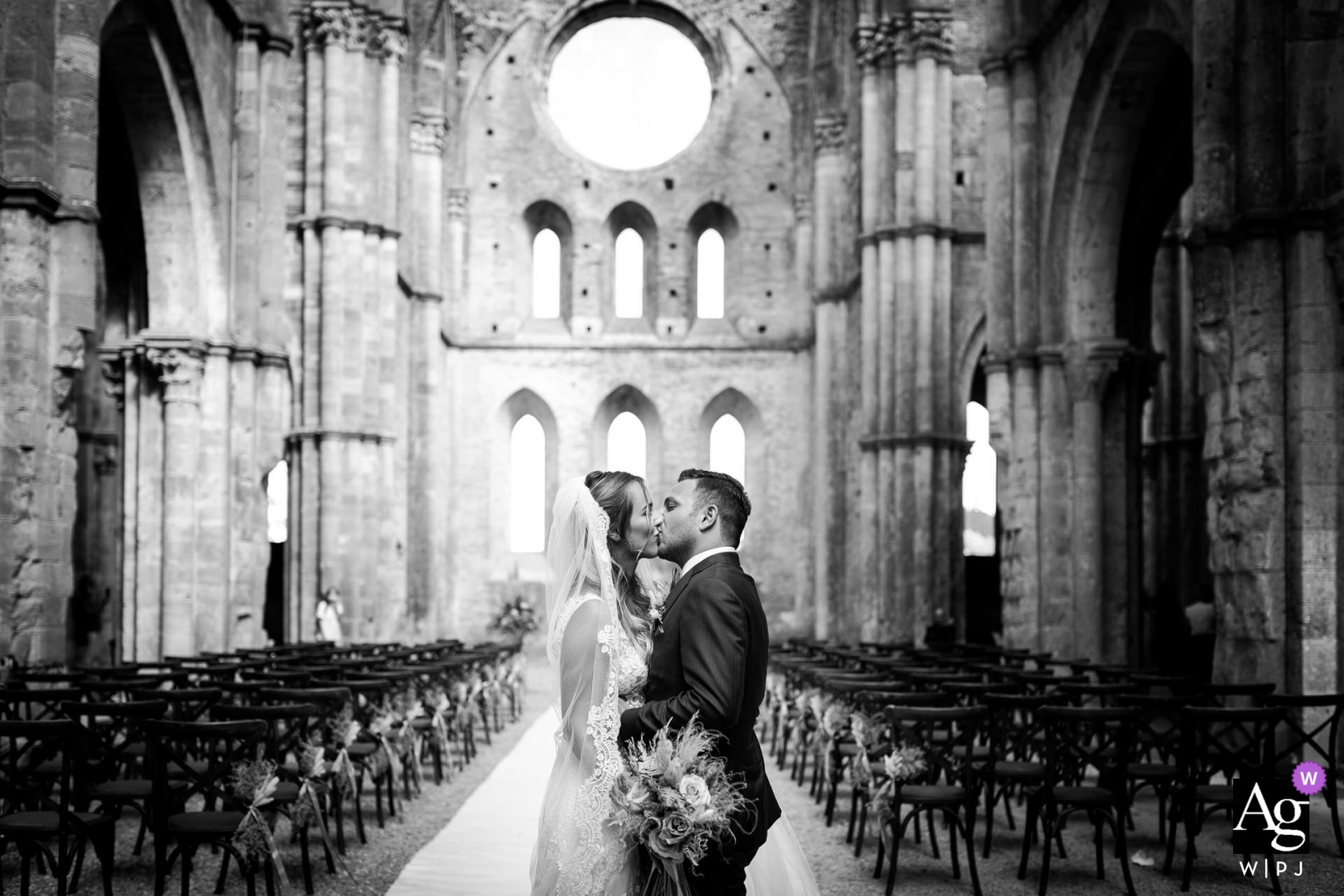 San Galgano Abbey, Siena, Italy fine art church ruins wedding couple picture of the bride and groom are kissing after the ceremony