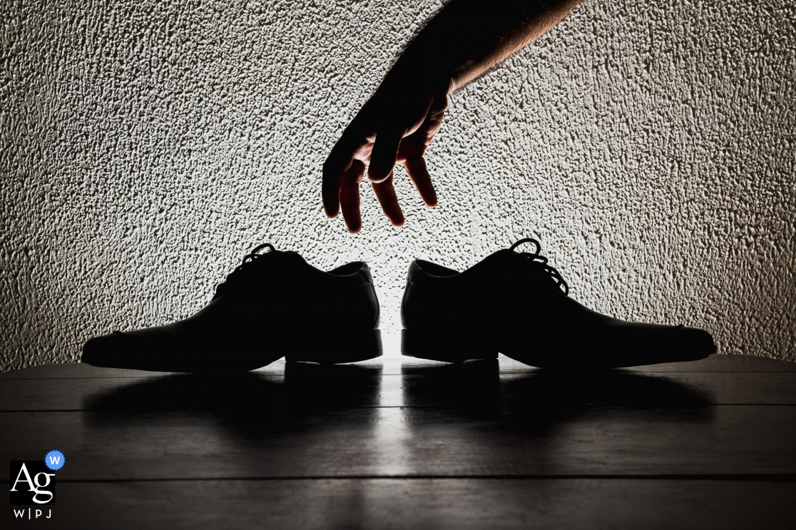 Artistic wedding photography from Hotel Quilombo, União dos Palmares-AL showing a silhouette of the groom's hand picking up his shoes