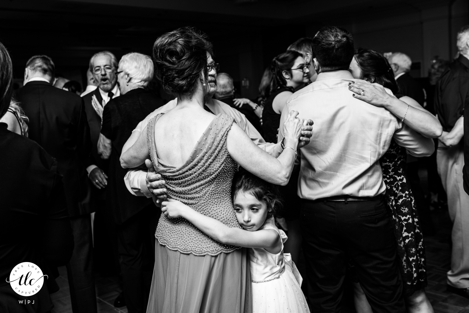Boston Marriott, Peabody MA documentary wedding image of a young girl hugging the leg of her grandmother during a wedding dance