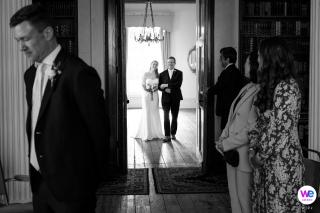 Escot House, Devon, Reino Unido Elopement Ceremonia Imagen | imagen en blanco y negro, el novio espera con anticipación mientras la novia se acerca