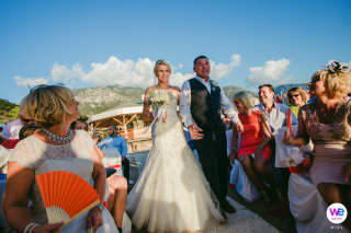 Sea Horse Beach Club, Oludeniz, Fethiye, Turkije Elopement Foto's | De bruid loopt met haar vader door het gangpad, aan weerszijden omringd door hun gasten