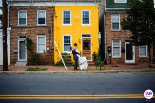 Alexandria, Virginia Elopement Photographer | The groom lifts the bride into the air as they stand in front of a bright yellow house on a street full of brick homes
