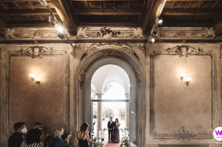 Italian Villa Elopement Photography | The bride and groom walk into a luxurious room in the Villa Litta Modignani