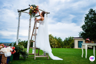 Hochzeitsfotografie von Villa Ekaterina in Vakarel, Bulgarien | Die Braut arbeitet in letzter Minute, um den Hochzeitsbogen zu perfektionieren