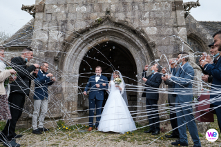 Western France, Brittany Wedding Photography | The bride and groom pass through the entryway of the Chapelle du Grouanec