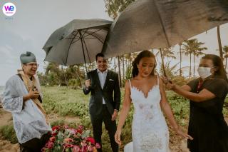 Fotografia di matrimonio in spiaggia | riparata dalla pioggia, la sposa cammina con grazia lungo la spiaggia