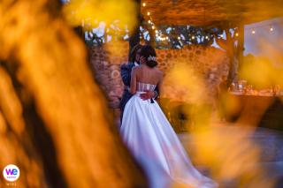 Photographie de lieu de mariage Avec des guirlandes lumineuses scintillantes servant de cadre pour le moment, les mariés partagent un baiser passionné