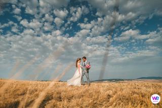 Portrait de mariage du couple italien alors que les vents portent la robe de mariée derrière elle dans les champs