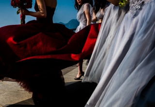 Wedding photography detail of bride and bridesmaids Preparing for the ceremony outside in the wind with their bouquets.