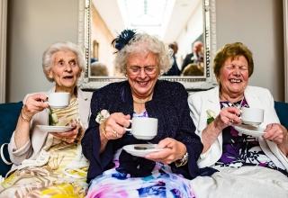在婚禮招待會的邊線故事攝影顯示女士從茶杯喝杜松子酒