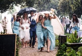 Zdjęcie oblubienicy i pana młodego z gośćmi przyłapanymi na deszczu w poszukiwaniu schronienia.