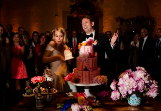 Fotografía de corte de pastel con la novia y el novio decidiendo si deben aplastar o no el pastel.
