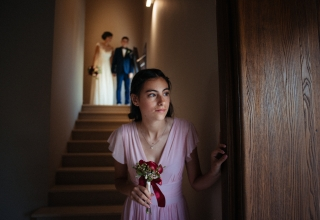Wedding Photographer captures quite moment as the bridesmaid looks timidly out before entering the scene