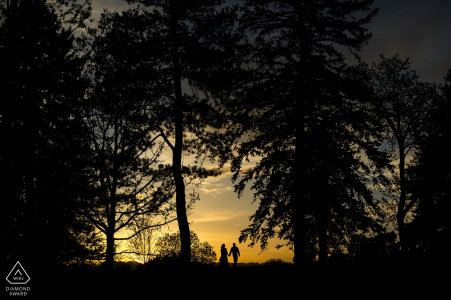 Boulder, CO Engagement Photographer. Silhouetted couple walking at sunset through tall trees.