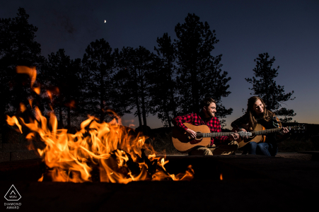 Prewedding photography of couple playing guitar and enjoying the evening by a fire | Colorado wedding engagements